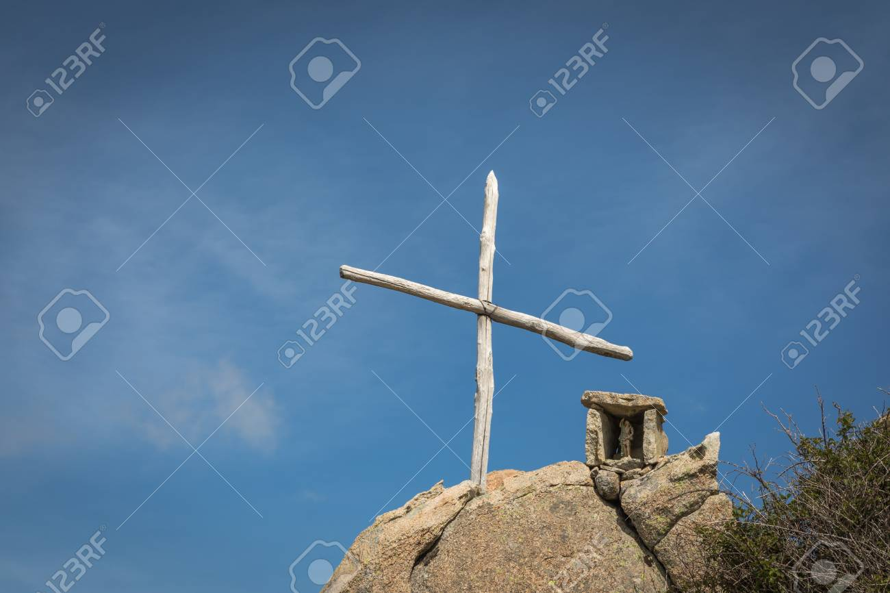 Wooden cross and stone memorial on a rock against a blue sky outside the Refuge de Prunincu on the route to Monte Astu in northen Corsica - 78103929