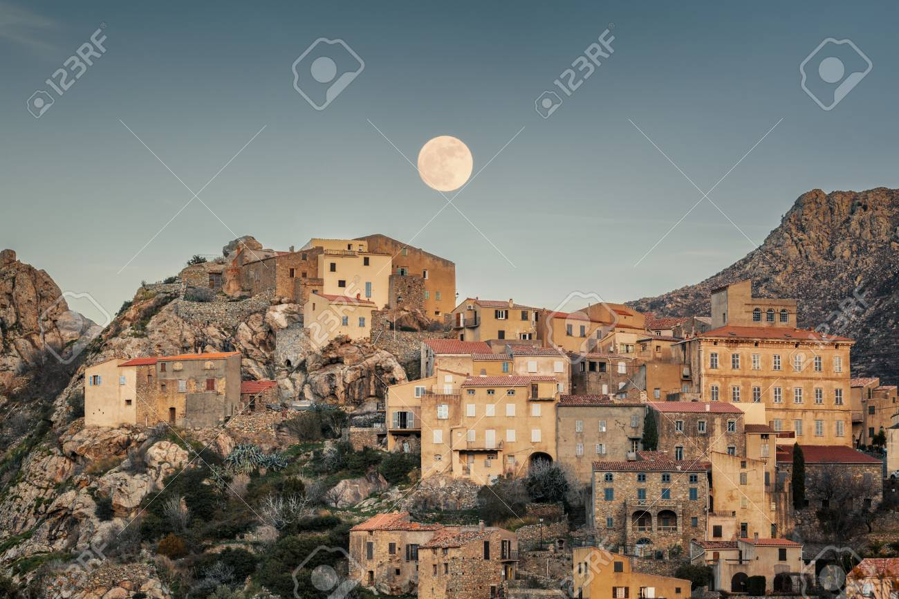 Full moon rising over the houses of the mountain village of Speloncato