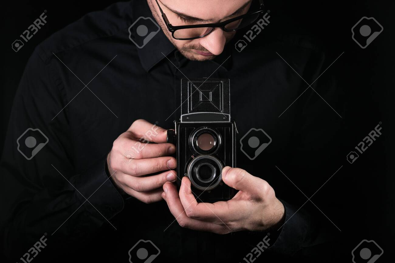 Man photographer holding a camera. - 120946965