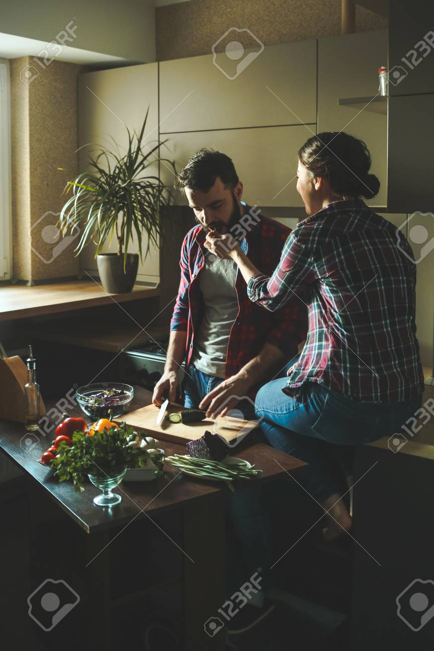 Beautiful young couple in kitchen at home while cooking healthy