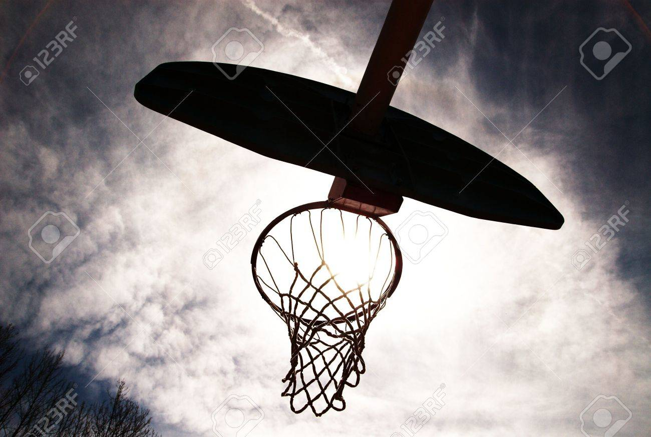 Basketball hoop shot from underneath. Backlit with sun coming through. - 2737239