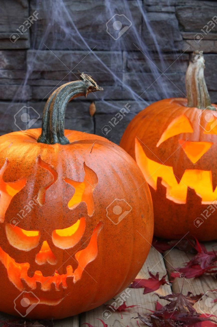 Carved pumpkins, lit with brick and spider web background Stock Photo - 5931078