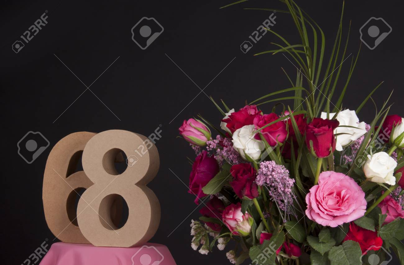 Age in figures next to a bouquet of flowers on a black background Stock Photo - 28649522