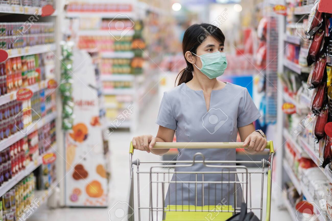 Young woman wearing protective face mask and shopping in grocery or department store protect coronavirus inflection. social distancing, new normal and life under covid-19 pandemic - 154945596