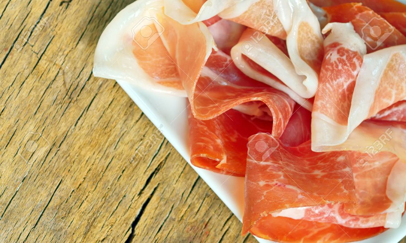 Slices of prosciutto on old wood Stock Photo - 21885635
