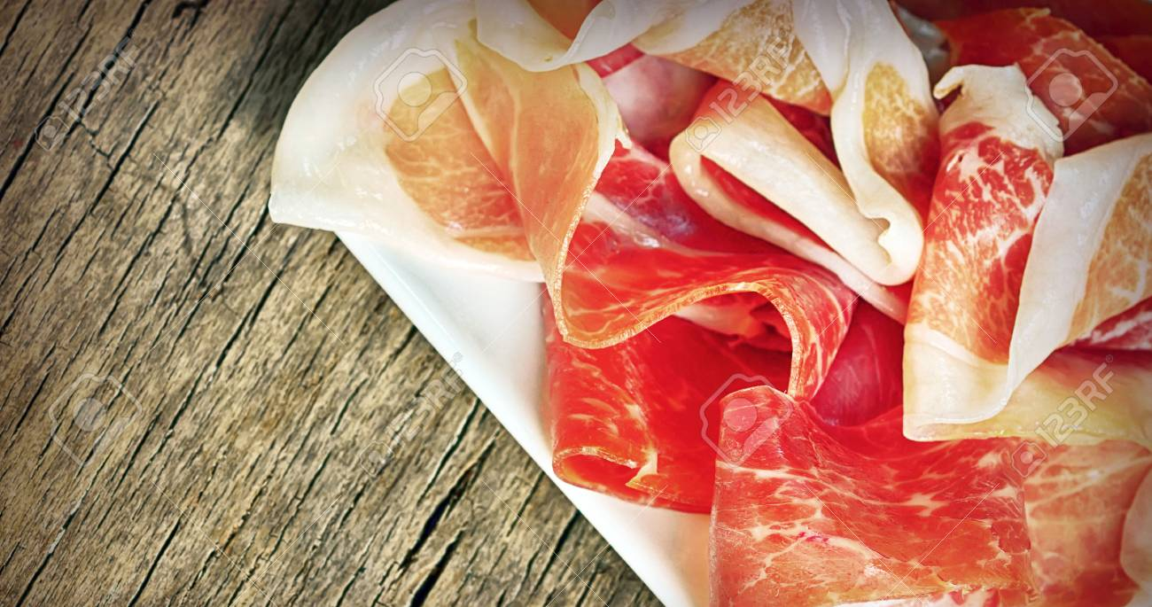 Slices of prosciutto on old wood Stock Photo - 21885636
