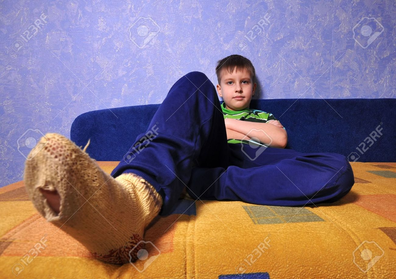 Boy wearing dirty socks with holes in them sits on sofa Stock Photo - 6476347