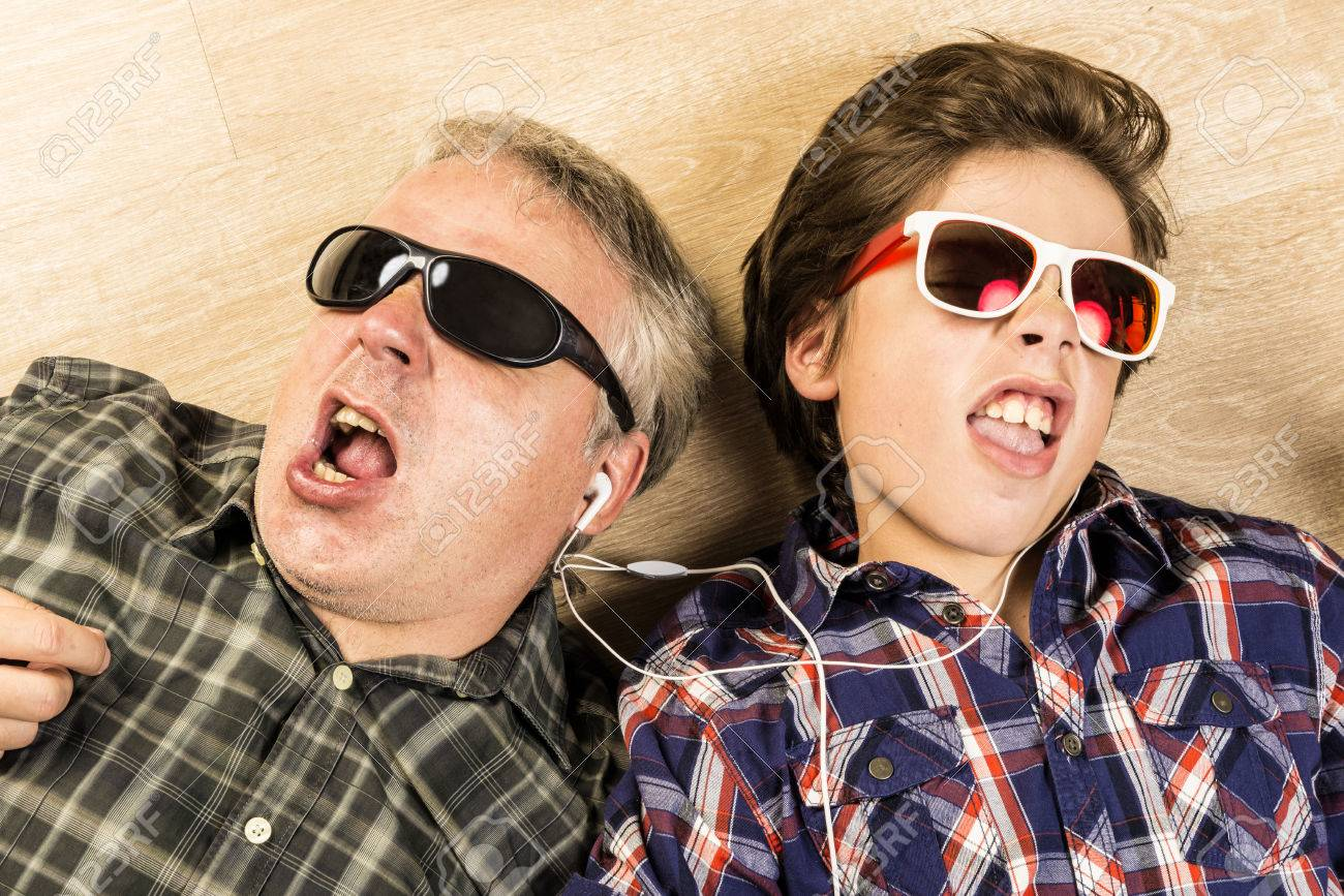 Father and son listening to music together with headphones stretched on a wooden floor at home - 43182856
