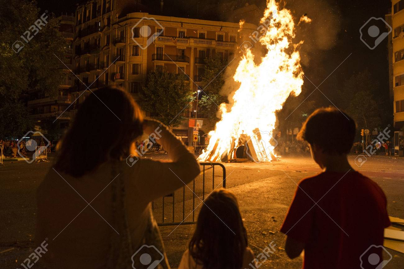 Family looking at a bonfire at night to celebrate the festivity of Sant Joan on a street in Barcelona, Catalonia, Spain - 54978796