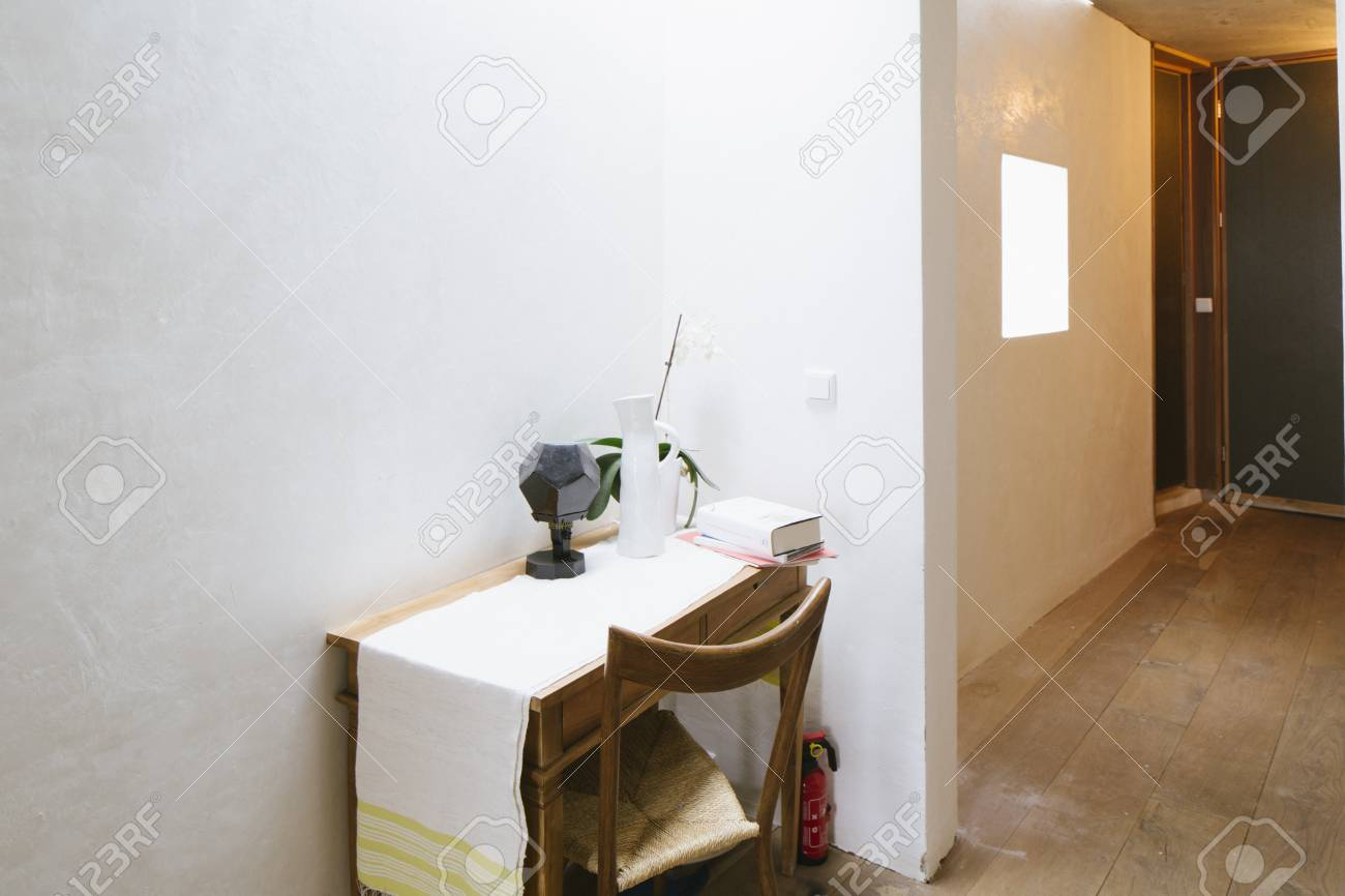 A Small Wooden Side Table With Chair And Decoration Objects In