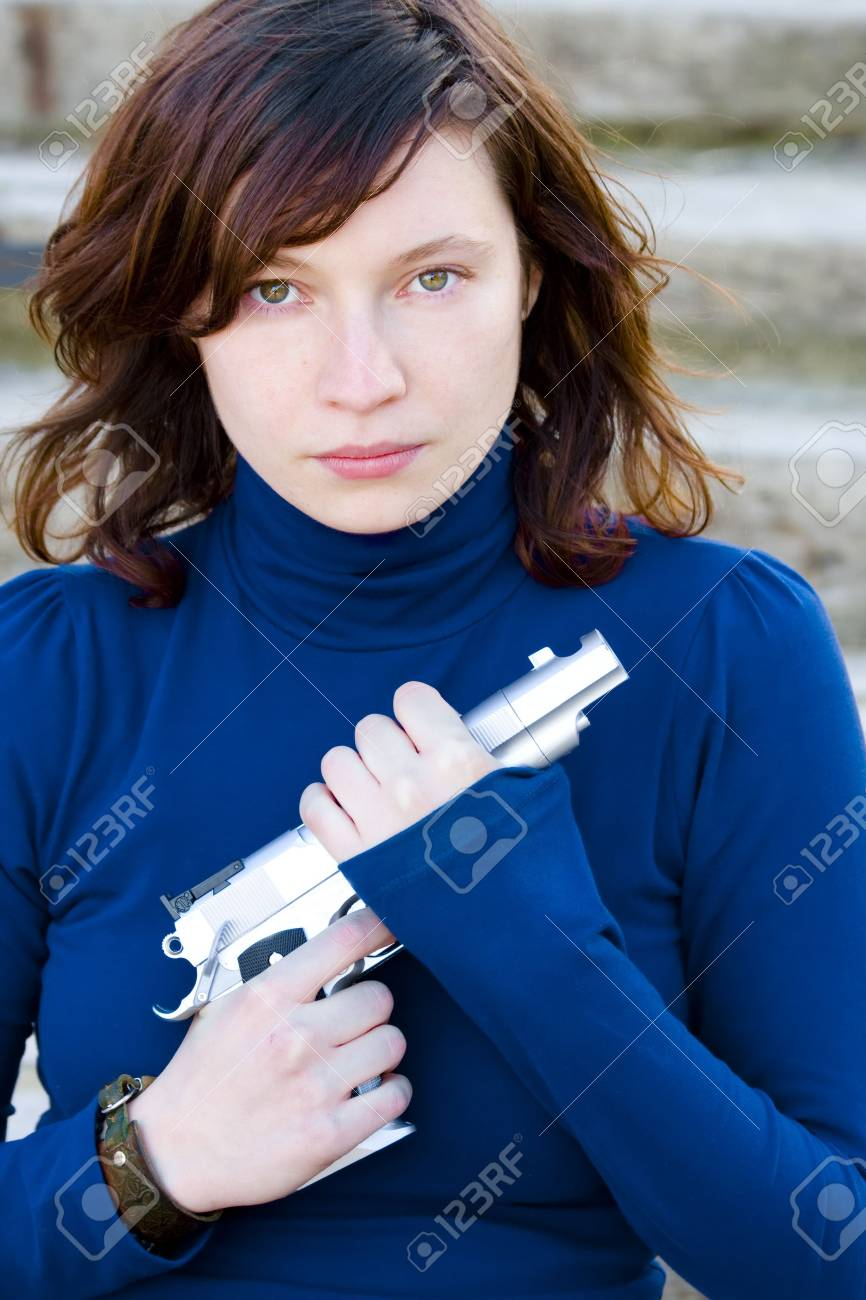 Red haired beauty with a gun in her hands Stock Photo - 2546426