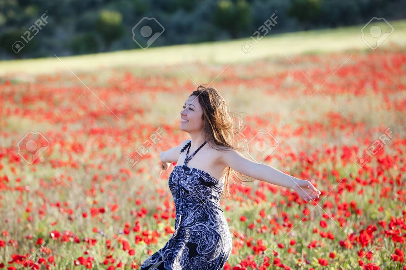 Young beautiful girl running on poppies field. Stock Photo - 7512877