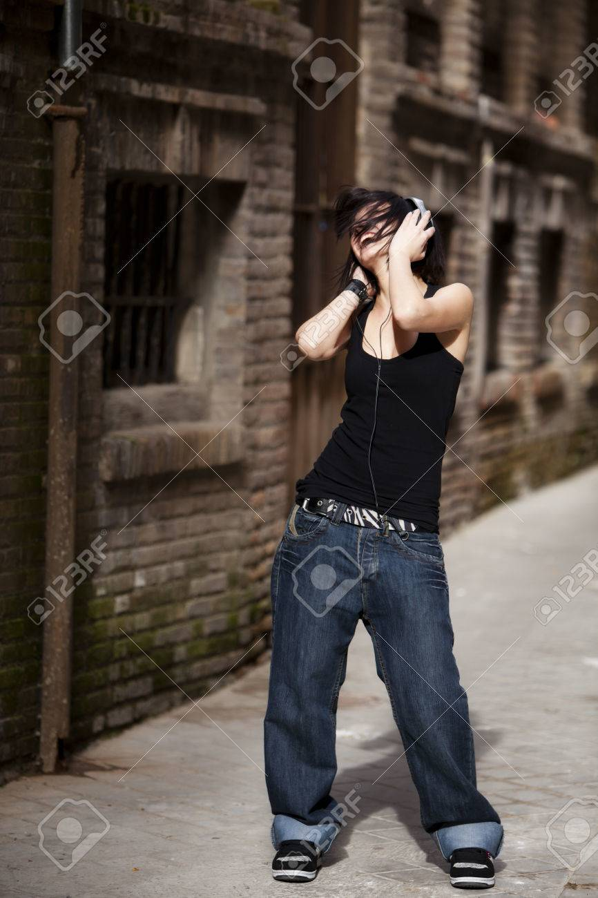 Young beautiful girl listening to music on urban background Stock Photo - 27084202