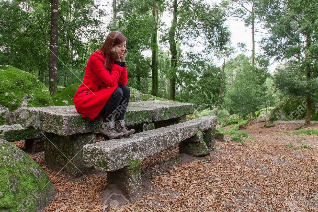 jeune sentiment femme déprimée assis sur une table et banc en pierre sur  une forêt de porter un manteau rouge pendant l'hiver