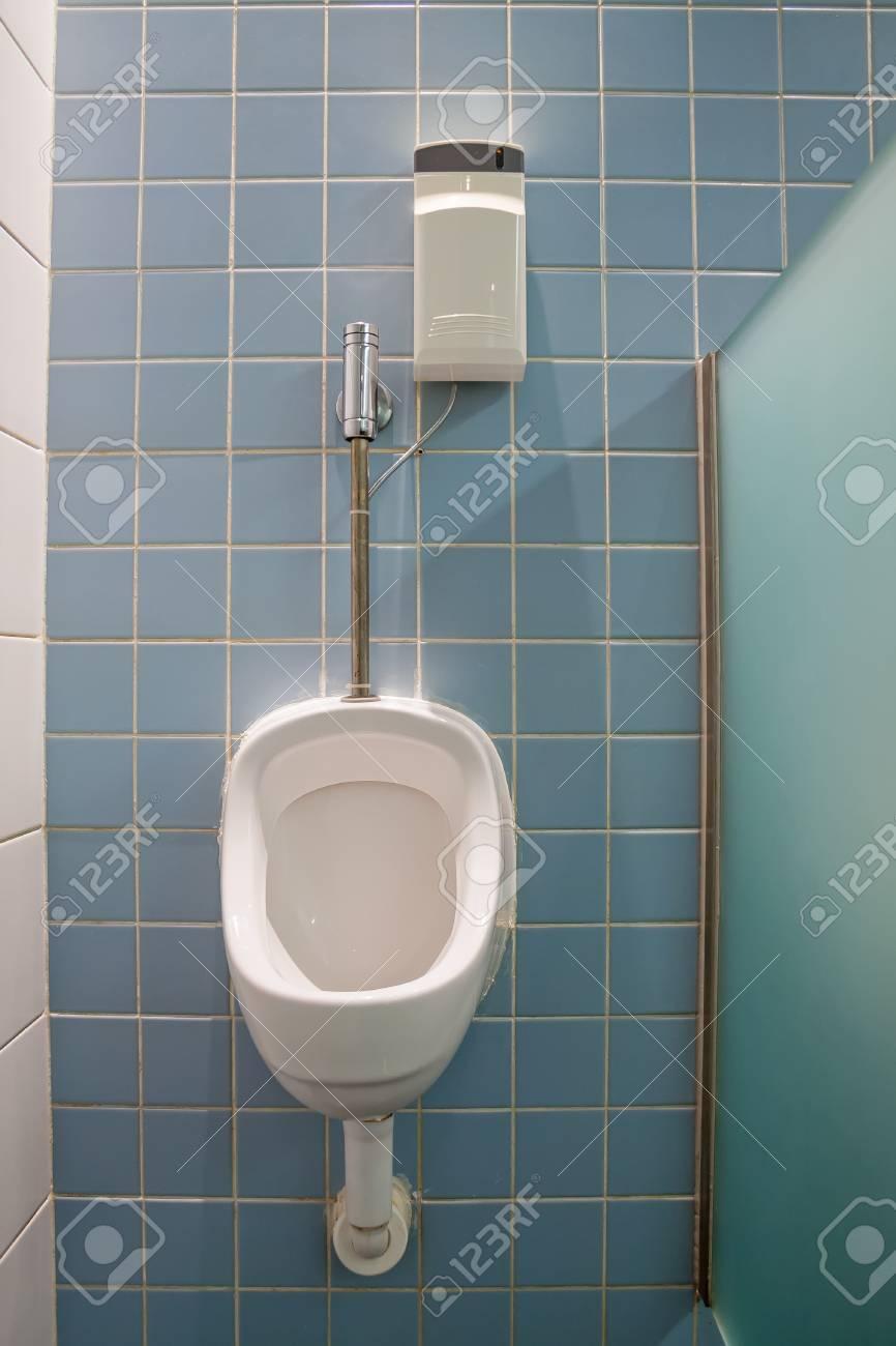 Urinoir avec un système déodorant sur une toilette publique avec des  carreaux bleus au mur