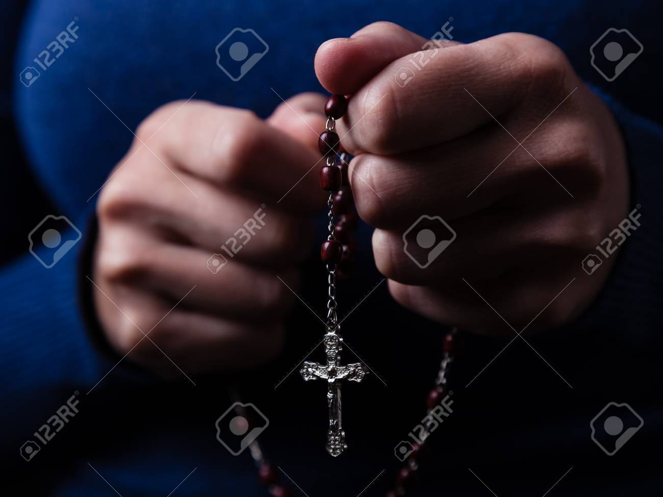2710f608f Female hands praying holding a rosary with Jesus Christ in the cross or  Crucifix on black