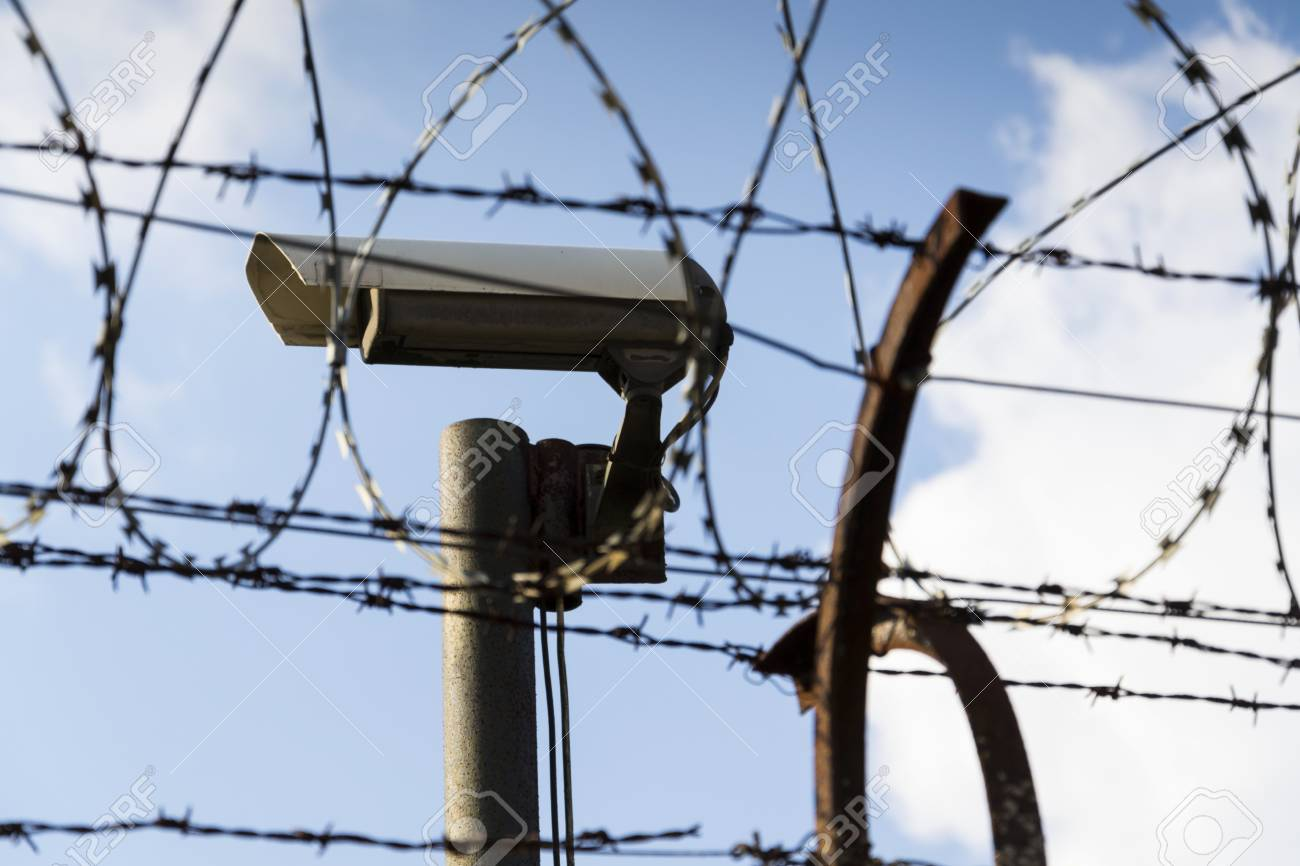 Security camera behind barbed wire fence stretched around prison.. on security camera sensor, security camera mounting base, security camera bulbs, security camera furniture, security camera voltage, security camera adapters, security camera cables, security camera components, security camera building, security camera painting, security camera features, security camera fittings, security camera software, security camera supports, security camera conduit, security camera junction boxes, security camera schematics, security camera mounting parts, security camera filter, security camera pinout,