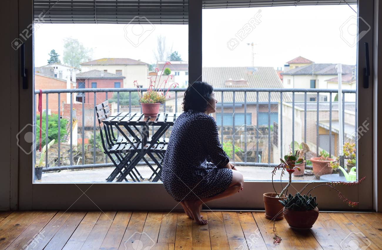 a sad woman looking out the window at home - 101143185