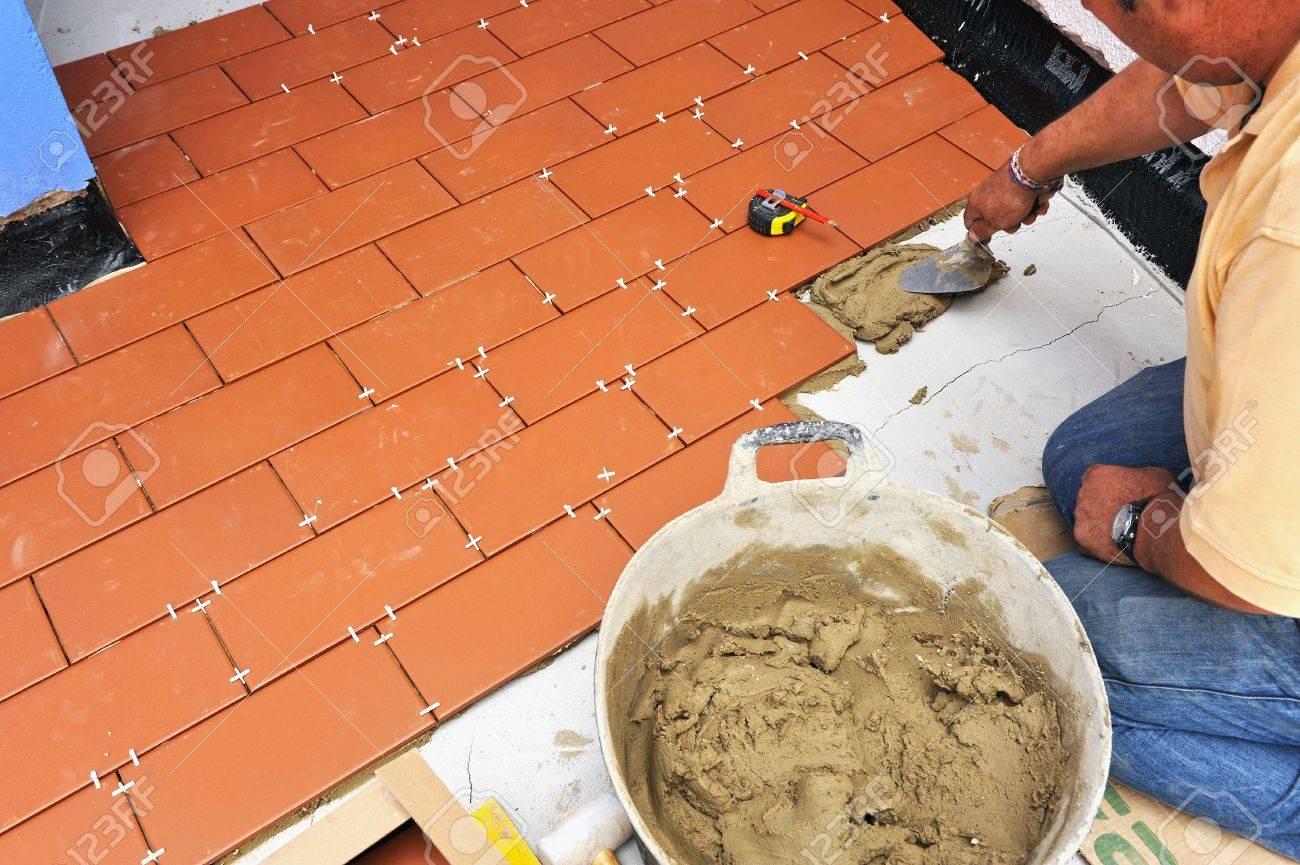 Trabajador De La Construcción Colocando El Suelo De La Terraza De Una Casa