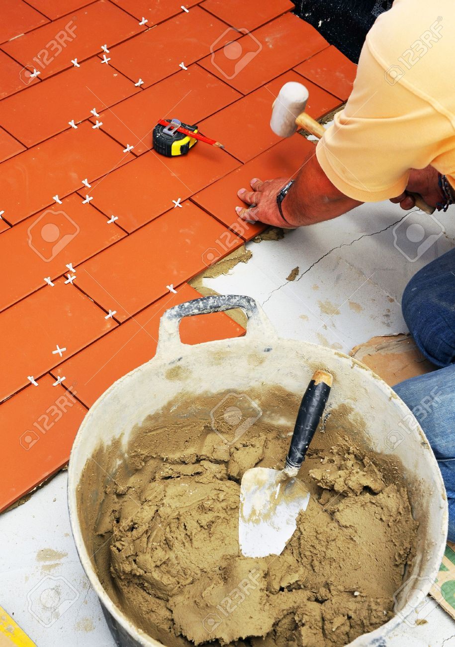 foto de archivo mason colocar el suelo de baldosas de una casa con cemento