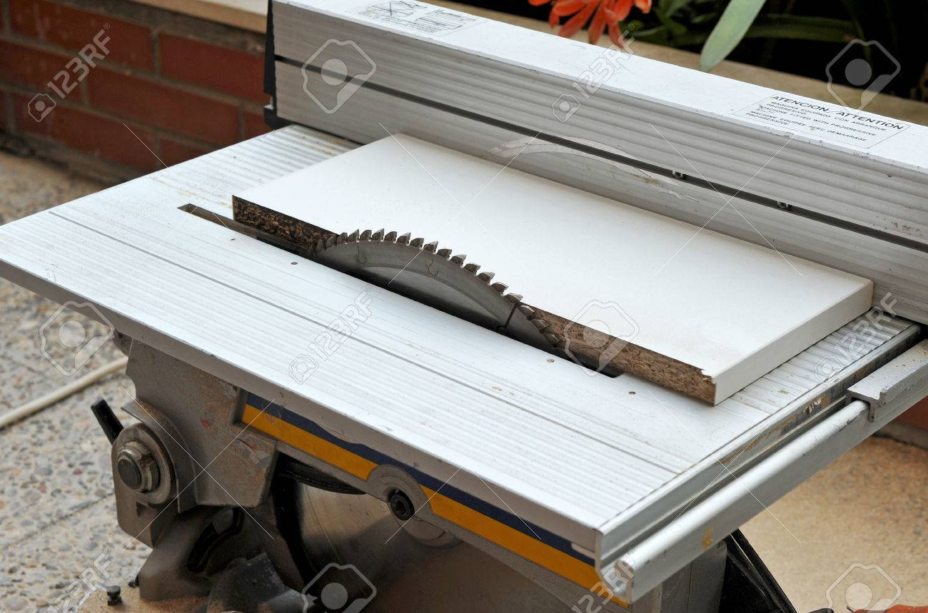 Cutting of a white melamine panel with electric saw disk