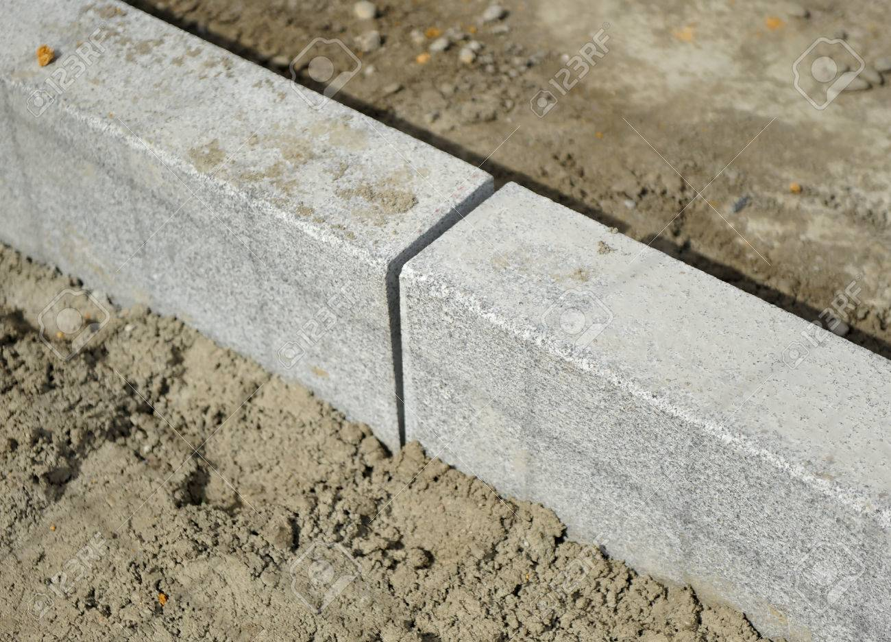 Laying granite curb on the sidewalk on a street