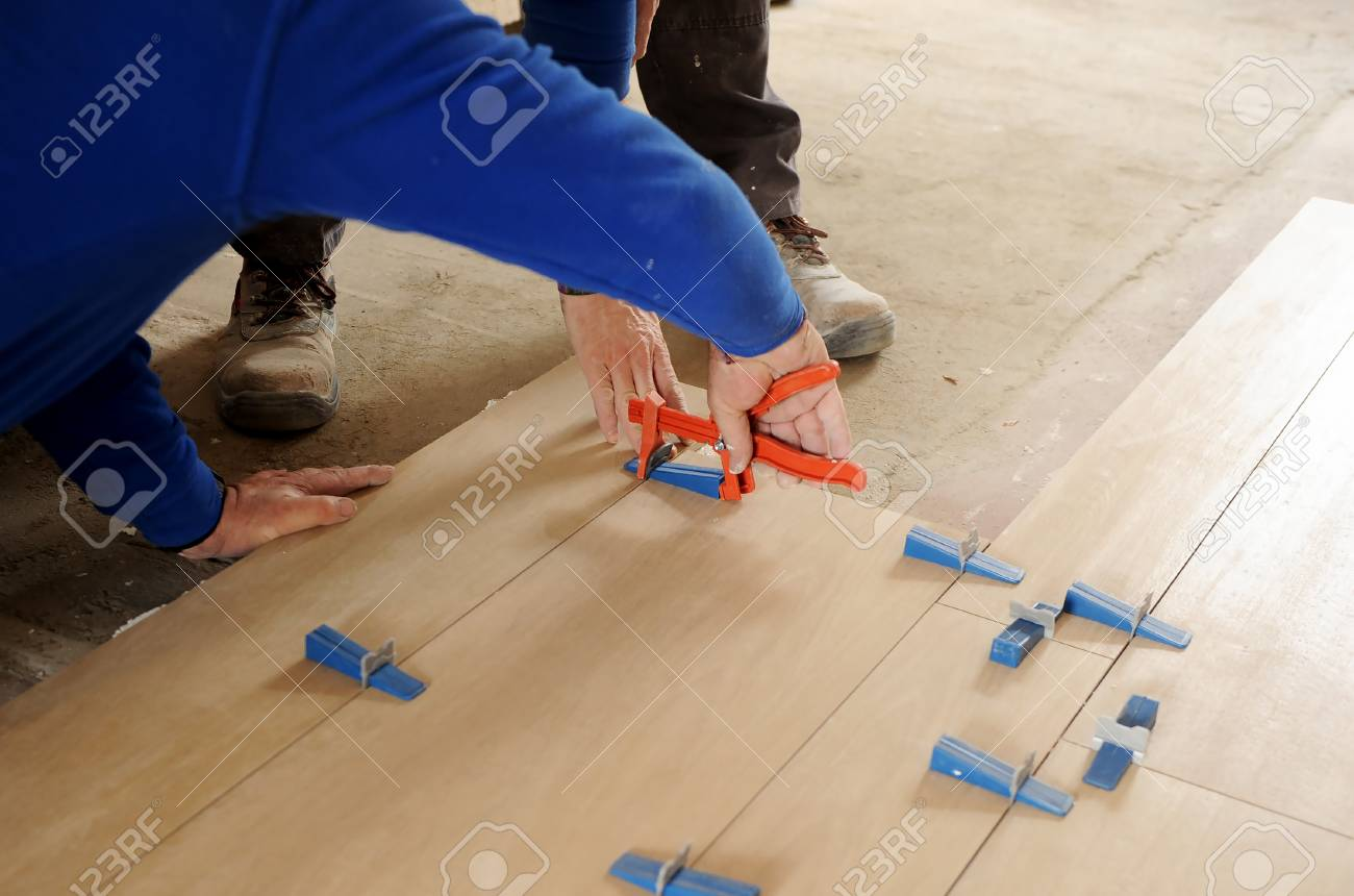 Construction Worker Placing A New Porcelain Tile Pavement In