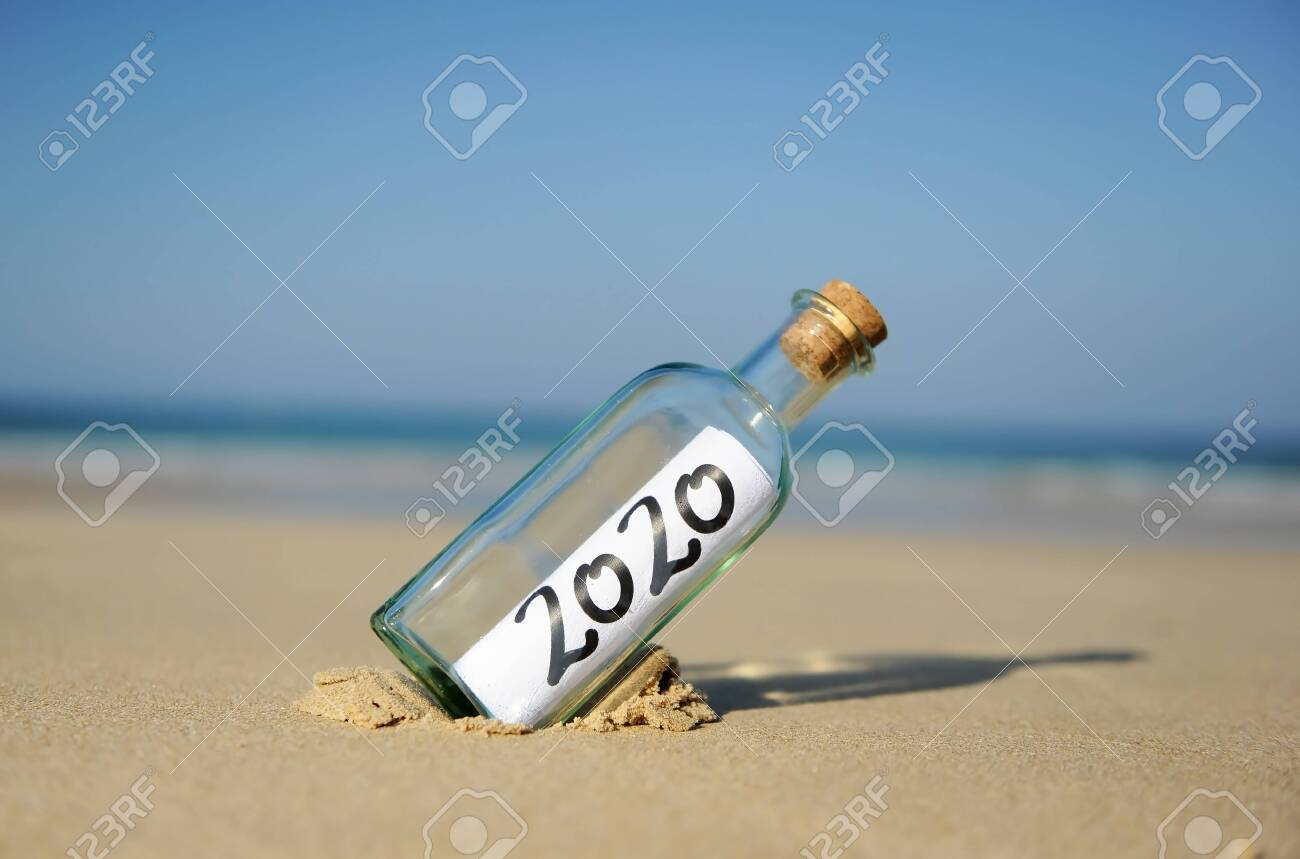 Happy New Year 2020, message in a bottle on the sand of beach. Summer vacation concept - 137845542