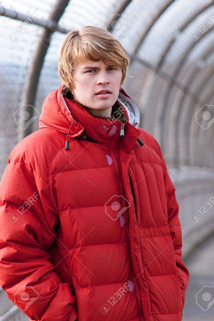A Guy In A Red Coat With Shaggy Hair Looks At The Camera While
