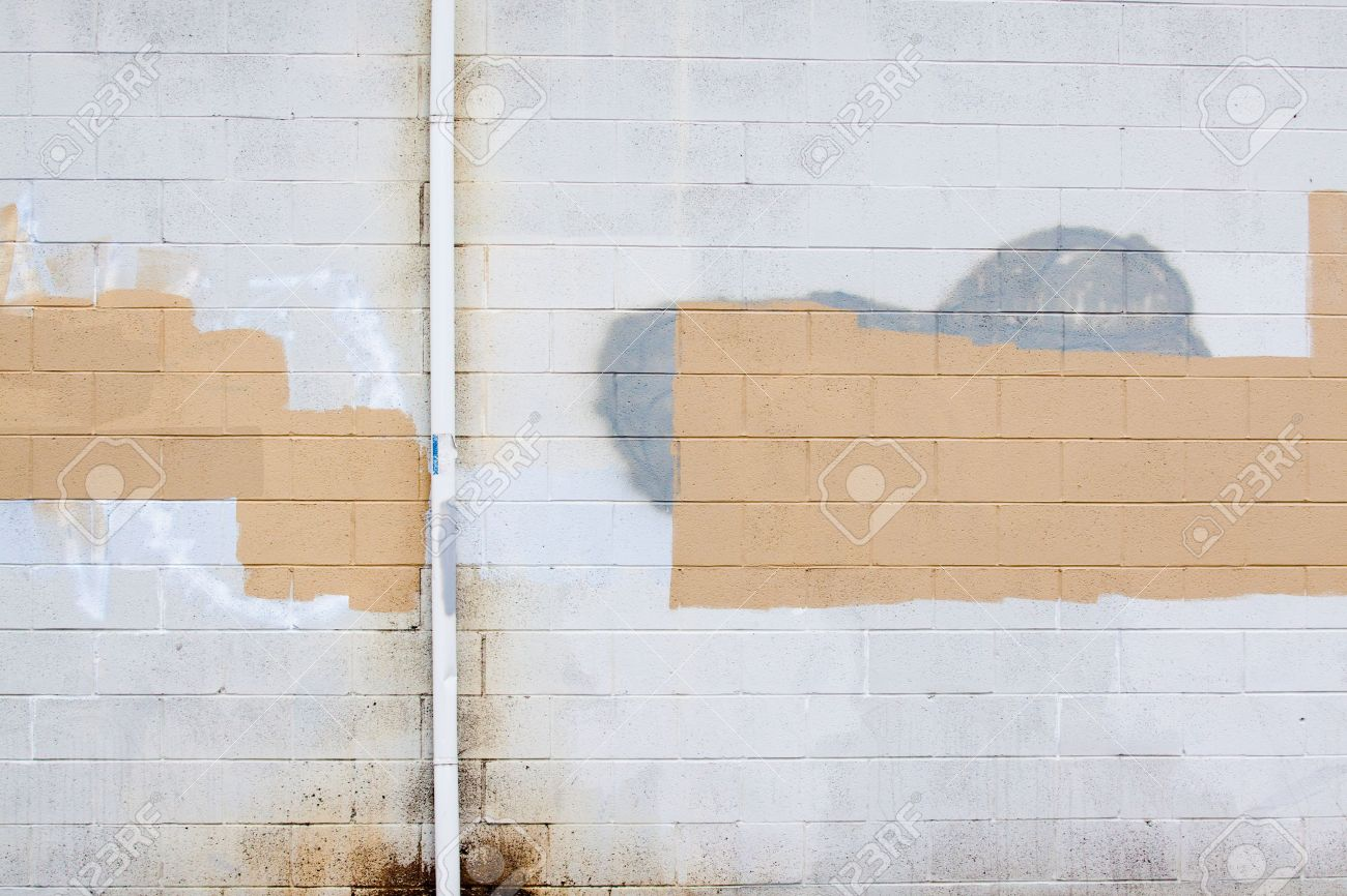 A grey wall has rectangular and square patches of paint used to cover up graffiti and vandalism along the side of an urban building. Stock Photo - 5729725
