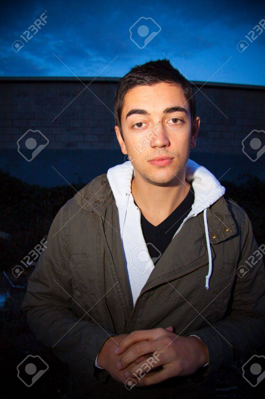 A man poses for some fashion photography at night wearing a modern..