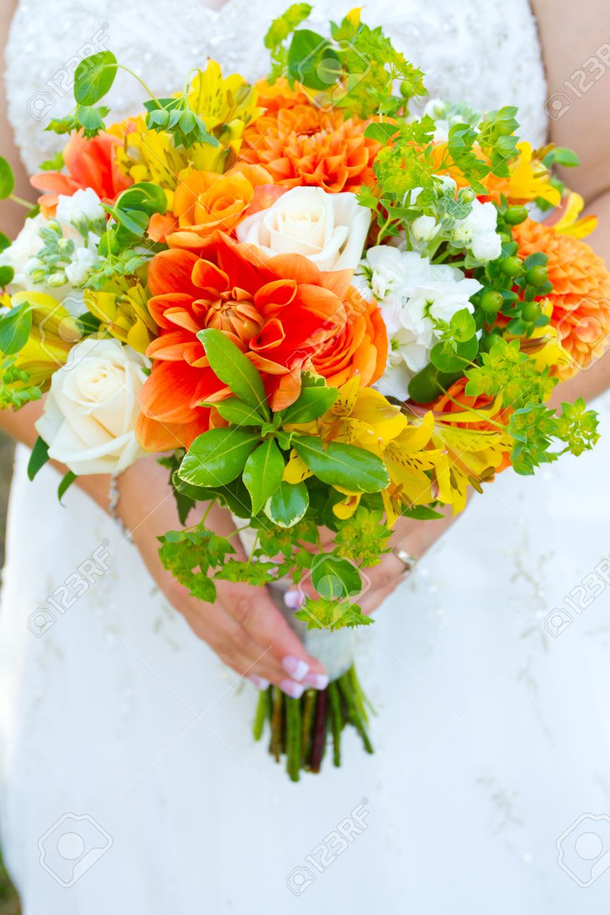 A bride in her white wedding dress holds her bouquet of orange a bride in her white wedding dress holds her bouquet of orange green and mightylinksfo