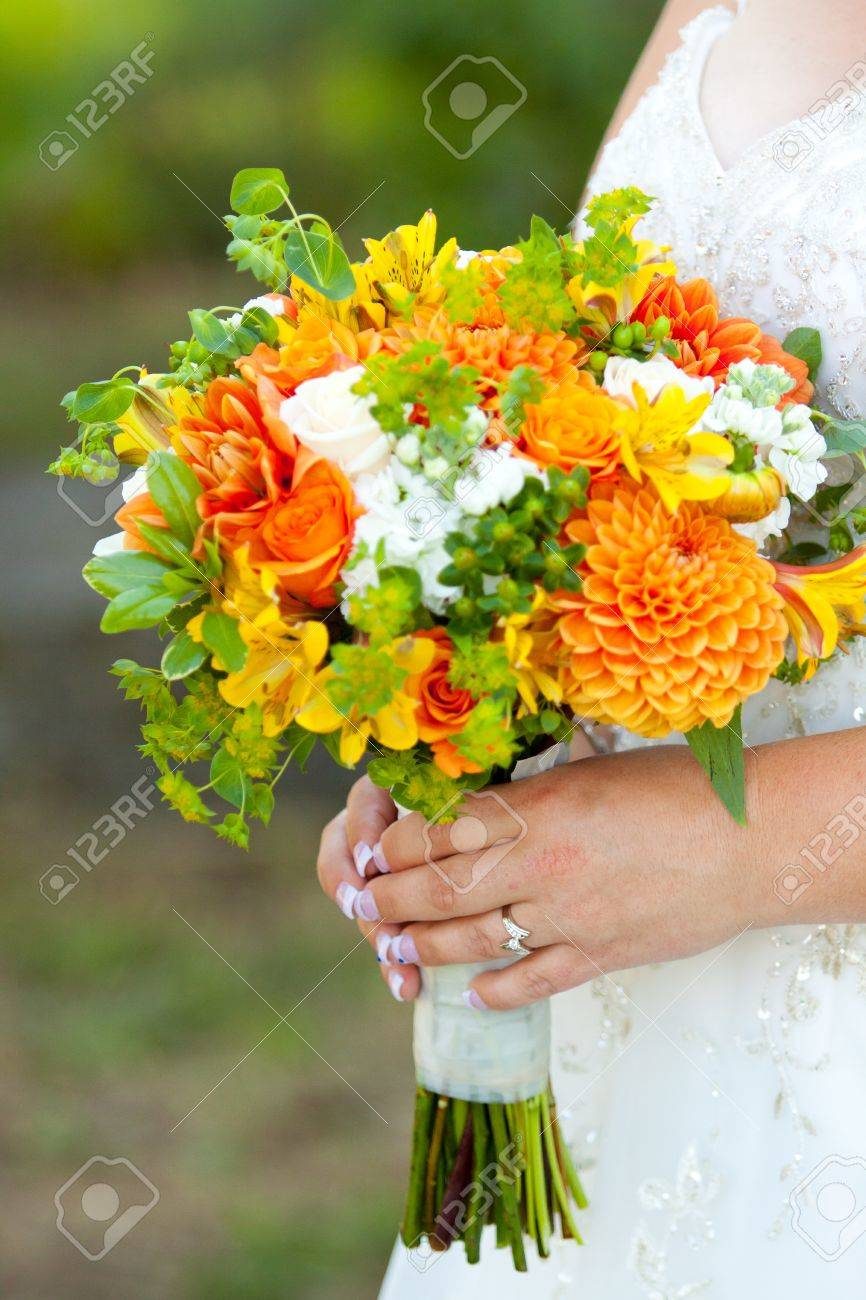 A bride in her white wedding dress holds her bouquet of orange a bride in her white wedding dress holds her bouquet of orange green and ombrellifo Choice Image