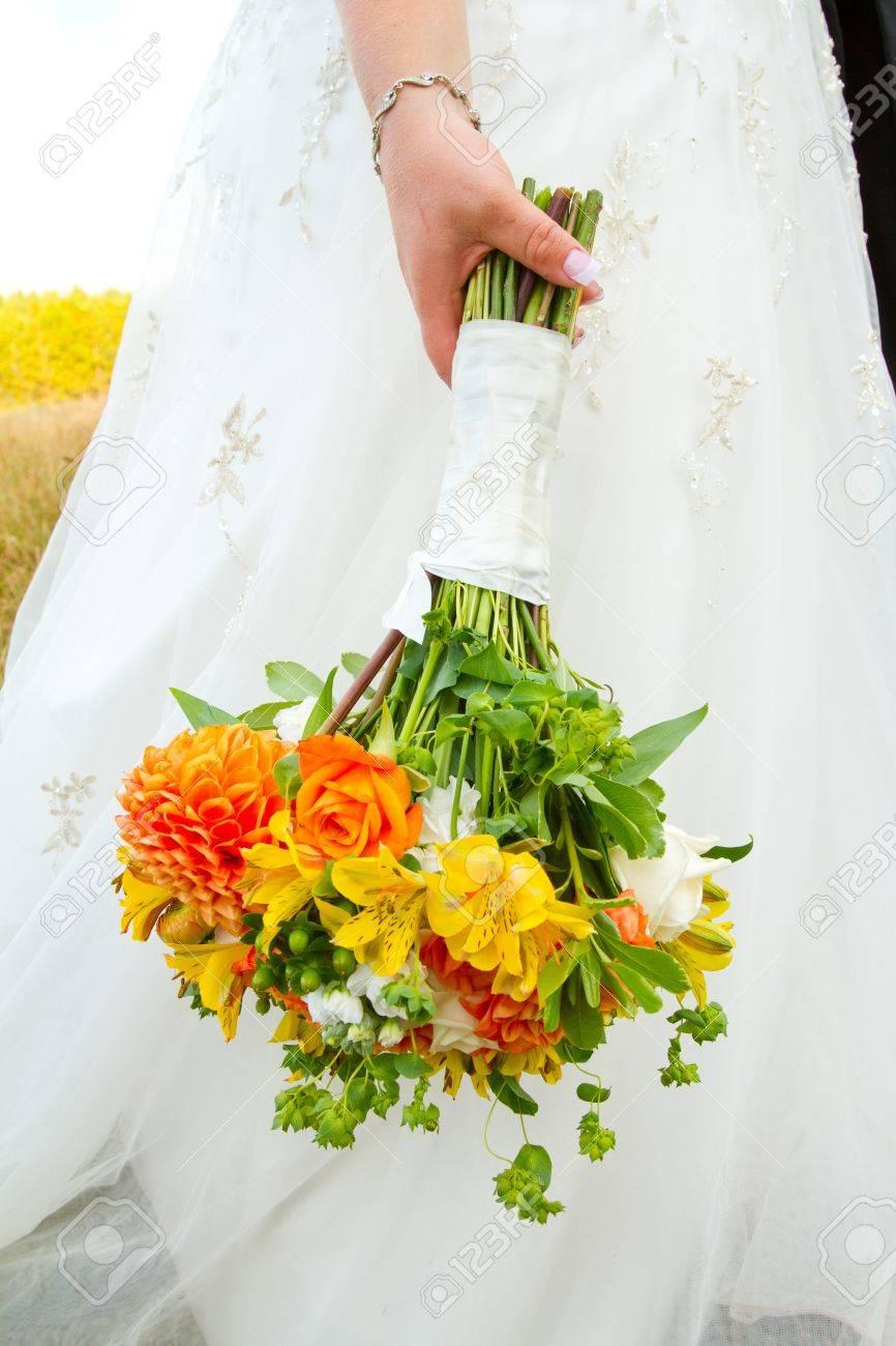 A Bride In Her White Wedding Dress Holds Her Bouquet Of Orange