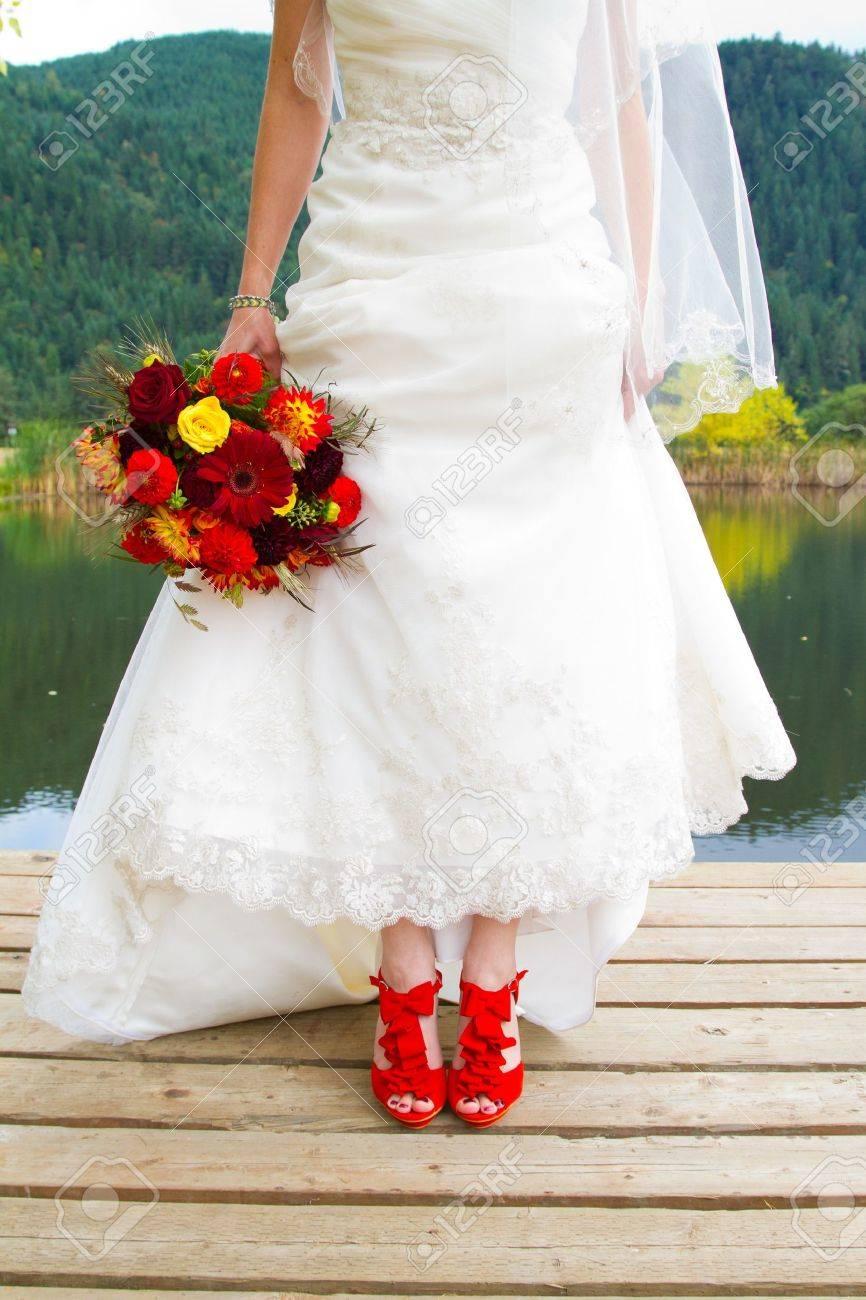 8814b9d2 Foto de archivo - Una novia vestida con su hermosos zapatos rojos de la  boda el día de su boda. Son stilettos de color vibrante.