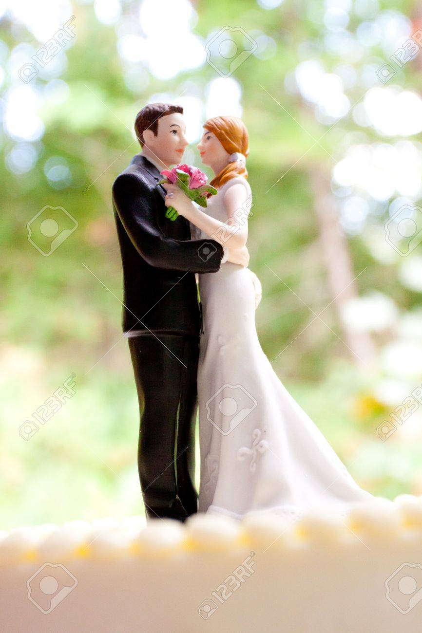 a bride and groom cake toppers stands atop this traditional white wedding cake at a reception