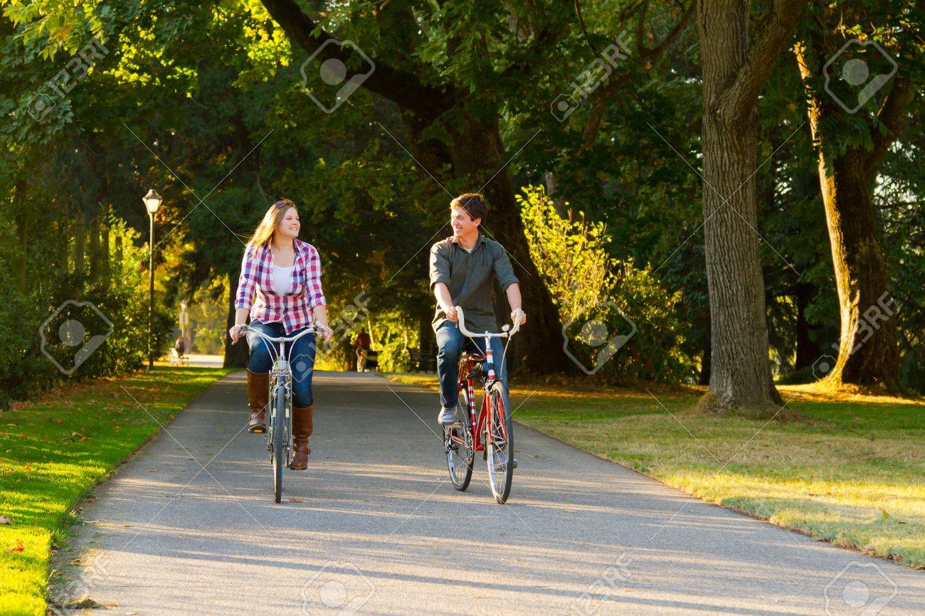 A man and a woman with their bicycles on a bike path in an outdoor park setting. Stock Photo - 17423927