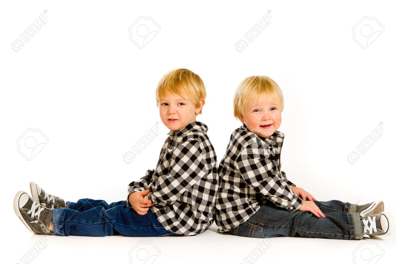 A boy and his sibling brother pose for this portrait in a studio against an isolated white background. Stock Photo - 17514906