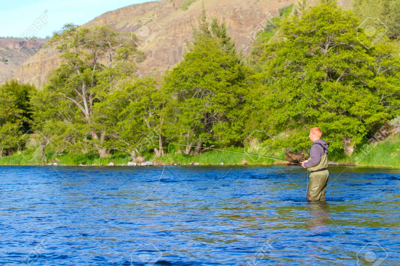 An experienced fly fisherman wades in the water while fly fishing