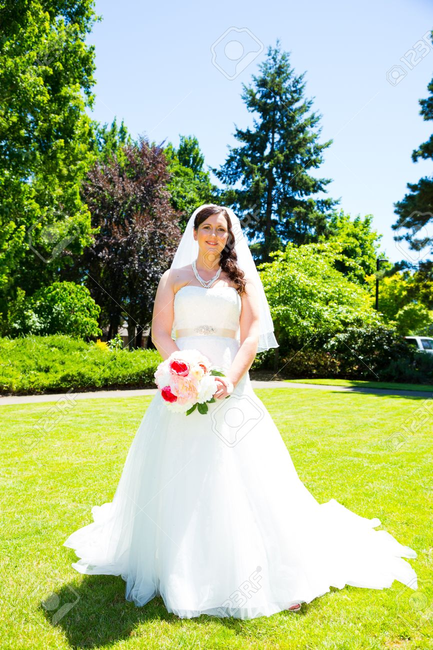 A Bride Poses For Some Portraits While Wearing Her Wedding Dress ...