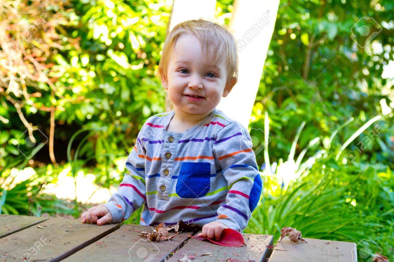 A One Year Old Boy Poses For A Picture While Playing With A Leaf