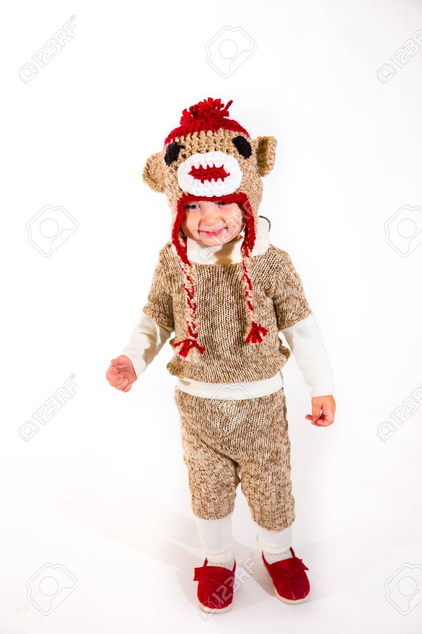 a two year old dressed up in a sock monkey halloween costume.. stock
