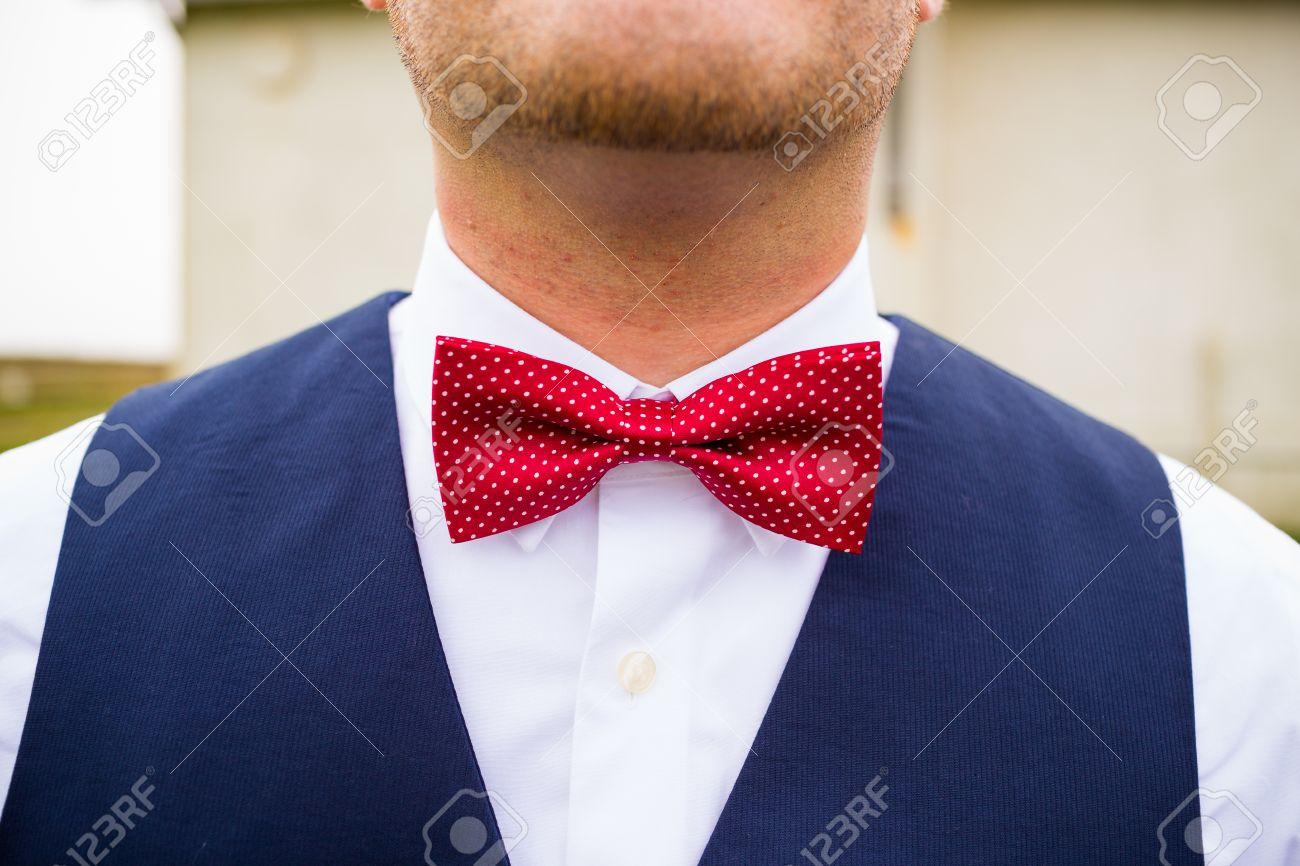 descuento especial de gran inventario diseño elegante Un novio de moda lleva una pajarita roja y blanca con un chaleco azul  marino en su día de la boda.