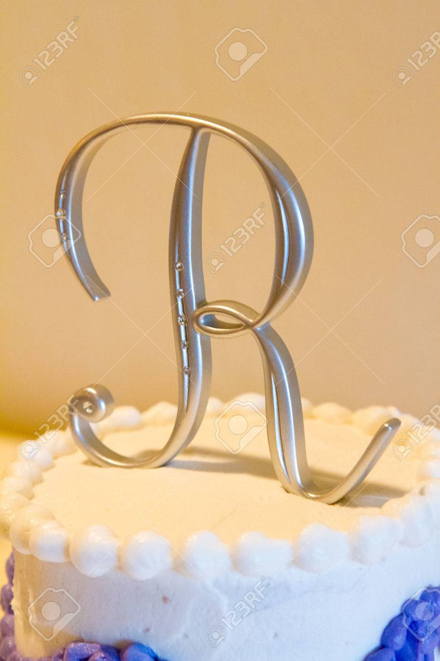 A Cake Topper With The Letter R On It On This White And Purple ...