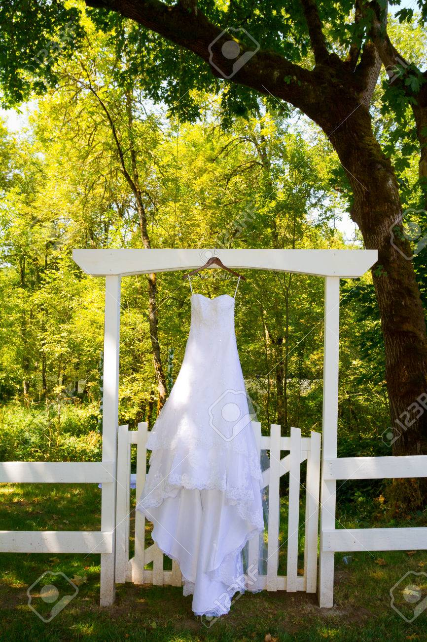 Beautiful White Wedding Dress Hanging Or Hung On A Gate Outdoors At Country Venue