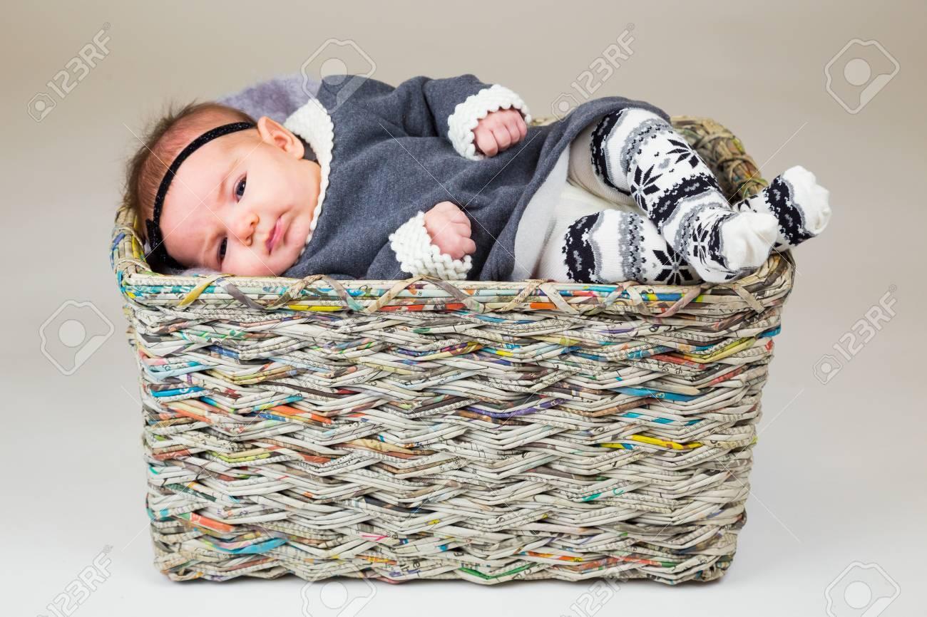 Canasta Para Bebe Recien Nacido.Bebe Recien Nacido Joven Que Llevaba Un Traje Lindo Que Presenta Para Los Retratos En El Estudio Con Un Fondo Blanco Sentado Dentro De Una Canasta