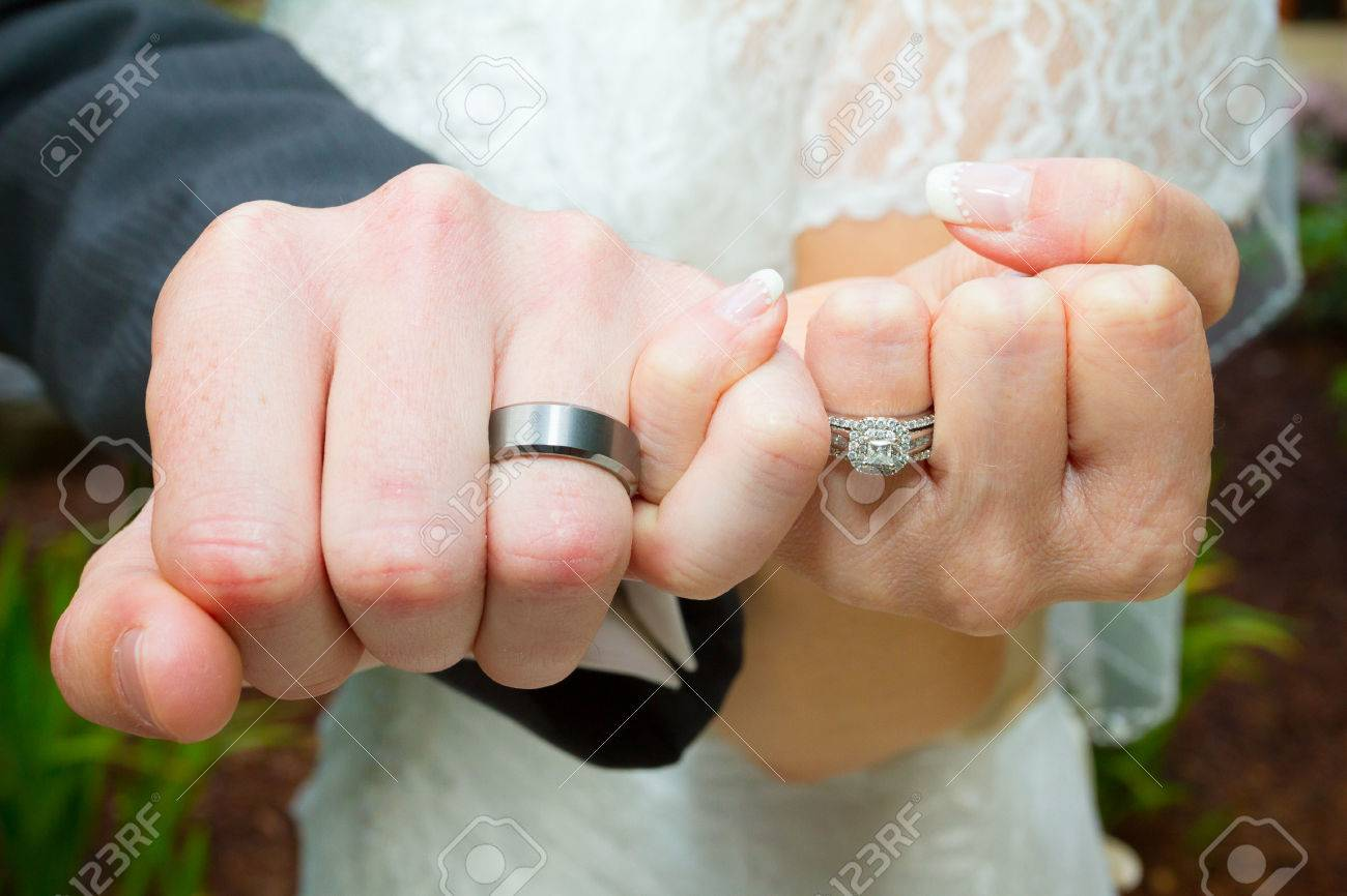Bride And Groom Put Their Hands Together In The Pinky Swear Position