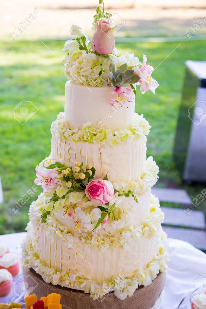 Grand Gateau De Mariage Blanc Avec Des Fleurs Traditionnelles Dessus Pour Le Dessert