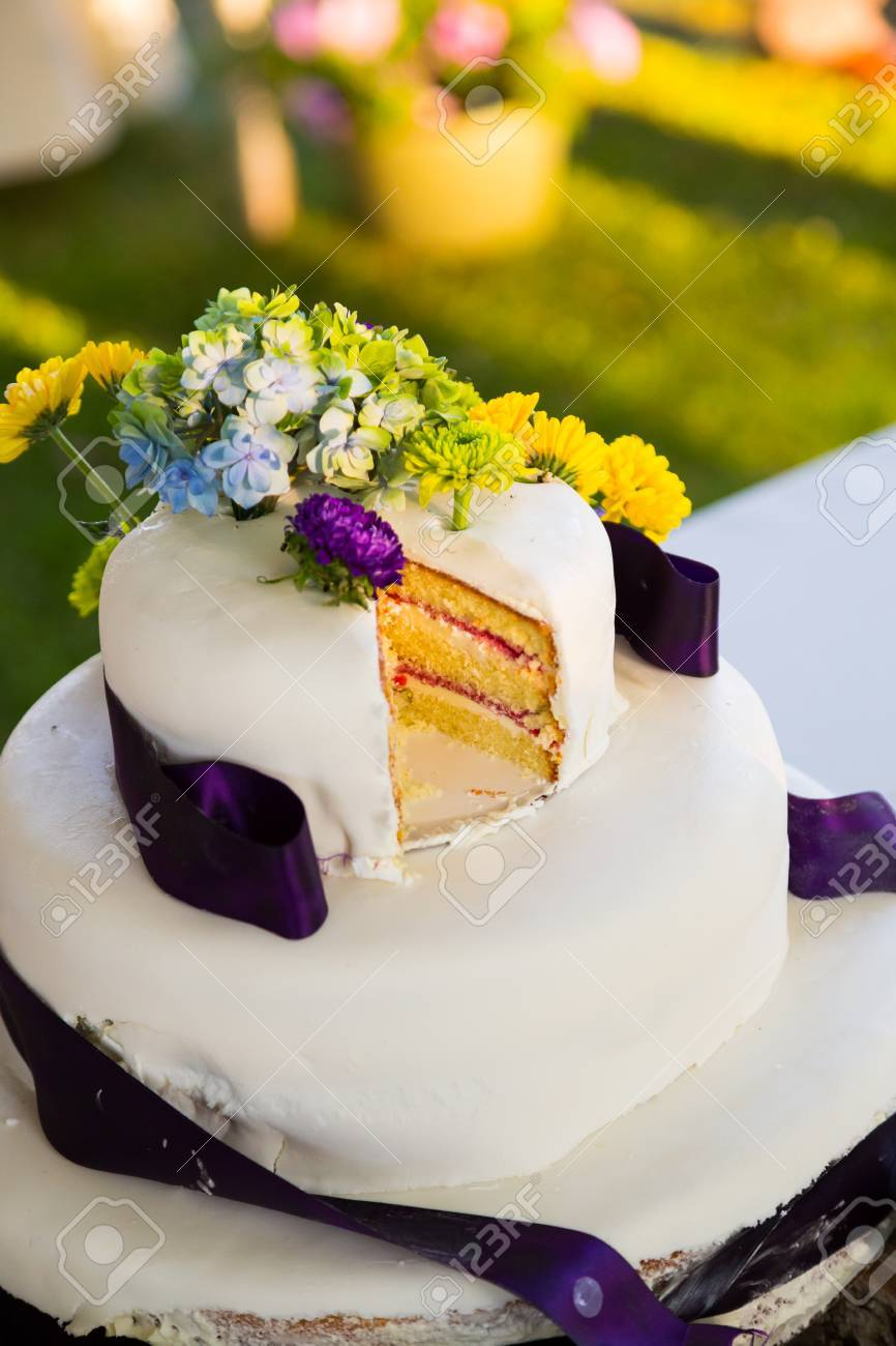 White And Purple Wedding Cake At The Reception For A Bride And ...