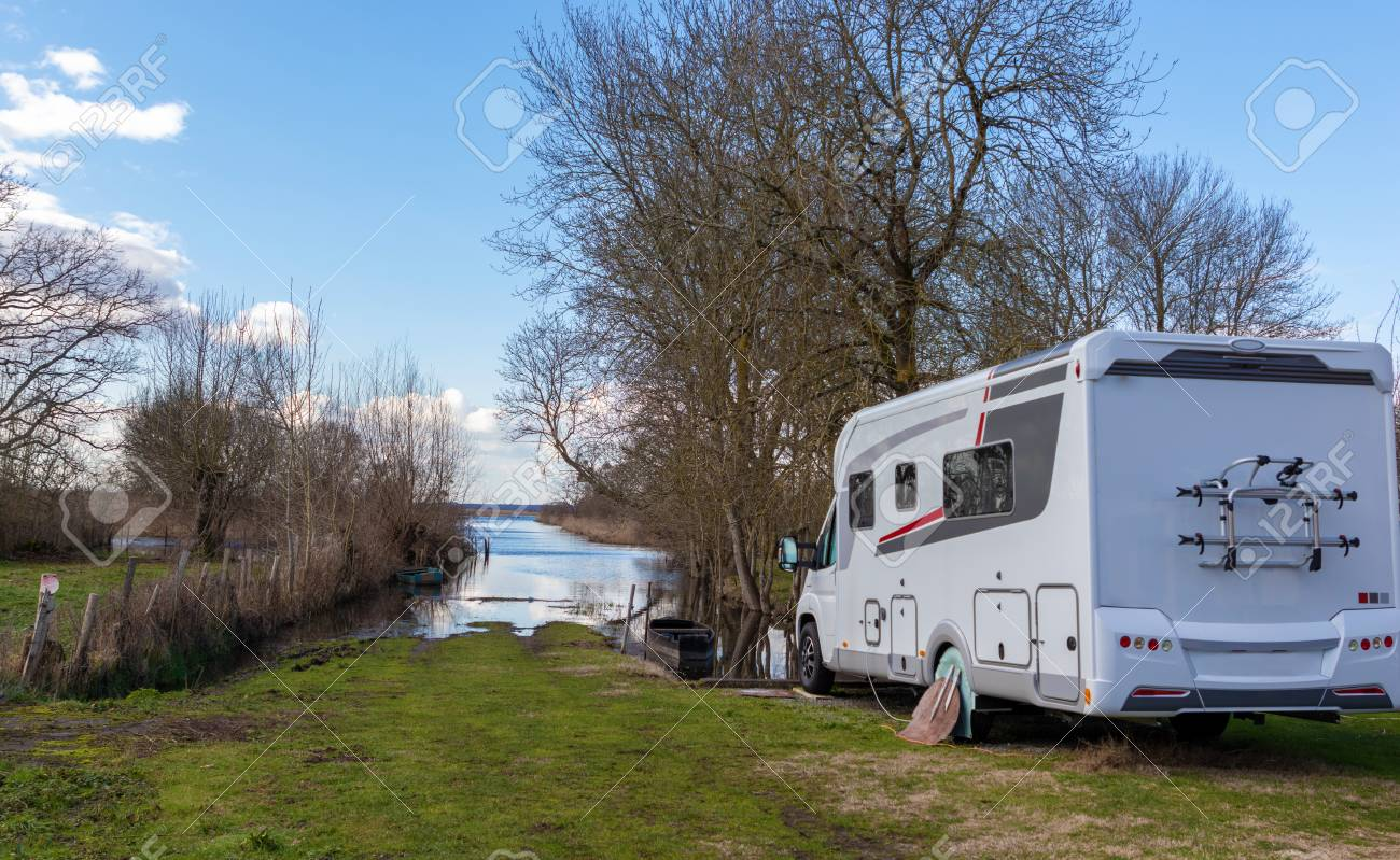 Camper In Front Of A Beautiful Natural Landscape With A Lake